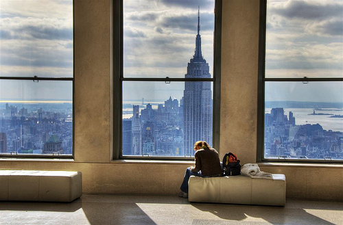 a_girl_reads_next_a_window_overlooking_new_york_city